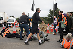 Enfield, UK. 15th September, 2021. An angry motorist moves an Insulate Britain climate activist blocking a slip road from the M25 at Junction 25 as part of a campaign intended to push the UK government to make significant legislative change to start lowering emissions. The activists, who wrote to Prime Minister Boris Johnson on 13th August, are demanding that the government immediately promises both to fully fund and ensure the insulation of all social housing in Britain by 2025 and to produce within four months a legally binding national plan to fully fund and ensure the full low-energy and low-carbon whole-house retrofit, with no externalised costs, of all homes in Britain by 2030 as part of a just transition to full decarbonisation of all parts of society and the economy.