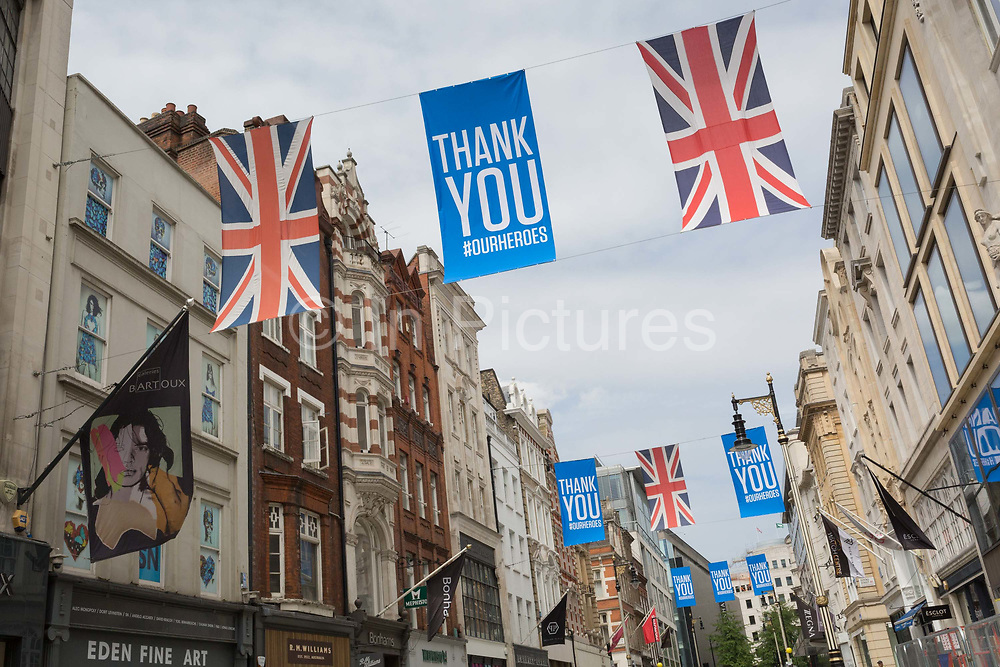 During the UKs Coronavirus pandemic lockdown and in the 24hrs when a further 255 deaths occurred, bringing the official covid deaths to 37,048, <br /> Union Jack flags and banners thanking NHS National Health Service key workers hang above fashion retailers and art galleries on New Bond Street, on 26th May 2020, in London, England.