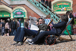 © Licensed to London News Pictures.04/05/2014. Brighton, UK. a man and woman relaxing on the beach enjoying the sunshine. Thousands of people are visiting Brighton during the May bank holiday weekend. Photo credit : Hugo Michiels. Photo credit : Hugo Michiels