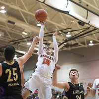 Gallup Bengal Isaac Bustinza (12) drives to the basket in Friday night's district 1-4A tournament championship game against Kirtland Central Broncos at Gallup High School in Gallup. The Bengals beat the Broncos 60-41.