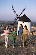 Four local girls stroll on a hill by a whitewashed windmill in Consuegra, La Mancha, Spain.