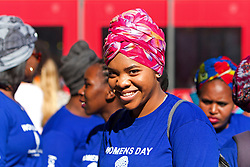 A woman smiles for the camera while wearing a headdress with others during the annual Women's Humanity Walk that takes place yearly on Women's Day. This year's walk was an intergenerational celebration of the 60th anniversary of the 1956 Women's March where 20000 women marched on the Union Buildings in Pretoria, South Africa to protest for freedom and justice. Women from all walks of life and all religious and cultural backgrounds marched together in solidarity and in remembrance from the Slave Lodge to the Artscape Theatre in Cape Town, South Africa on the 9th August 2016.<br /> <br /> Photo by:   Mark Wessels / Real Time Images.