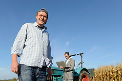 Farmer smiling, portrait, businessman with laptop in background, Bavaria, Germany