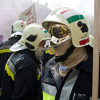 Protesters are reflected in the helmet of a protesting fireman walking in smoke produced by a grenade of the protesters during an anti-government rally in Budapest, Hungary on April 16, 2011..Thousands of Hungarians, including policemen and firefighters, on Saturday protested against the government's austerity measures. The government has launched a package of fiscal reforms to cut the budget deficit, including scrapping early retirement, which mostly affects law enforcement personnel.