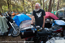 Billy Mitchell doing some maintenance on his bike in the campground by the Cabbage Patch before the return ride of 4,600 miles to Washington state. Daytona Bike Week. FL, USA. March 12, 2014.  Photography ©2014 Michael Lichter.