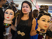 24 JULY 2013 - BANGKOK, THAILAND:  A woman carries haircut mannequins through the show floor at the Hairworld Festival in Siam Paragon, an upscale shopping mall in Bangkok, Thailand.        PHOTO BY JACK KURTZ