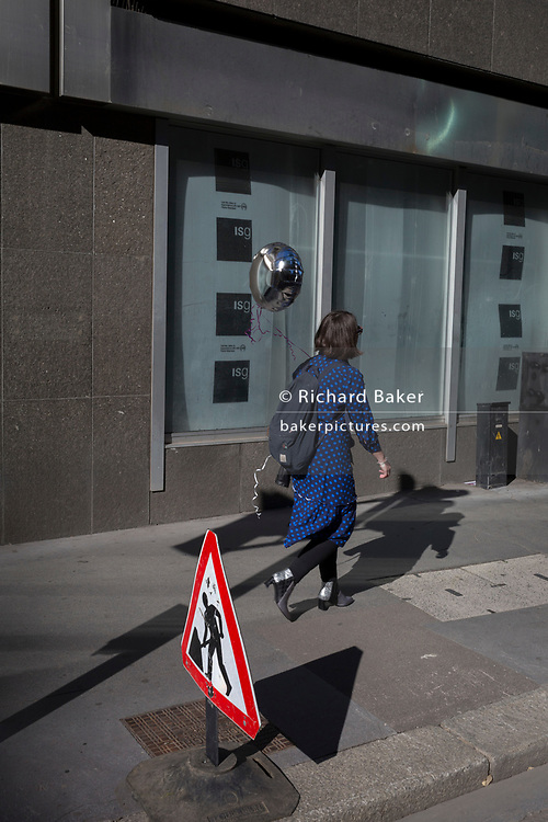 A lady varries a balloon along Fenchurch Street in the City of London, the capital's financial heart (aka The Square Mile), on 26th September 2018, in London, England.