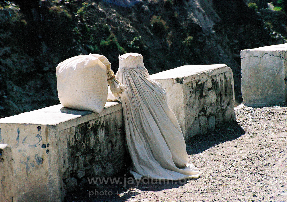 Pakistan, Northwest Frontier Province, 2004. Looking much like the heavy sack she is transporting, a woman waits for a ride. All-covering burqa are often seen in parts of Pakistan's NWFP.