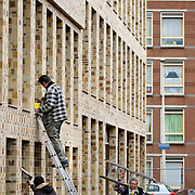 Nederland Den Haag 26 november 2008 2081126 Foto: David Rozing..Bouwvakkers aan het werk bij bouw nieuwbouw woningen in de achterstadswijk Schilderwijk. Veel oude woningen zijn gesloopt en vervangen door nieuwbouw, dit om verpaupering etc tegen te gaan. .De schilderwijk is een van de 40 wijken van Vogelaar. Deze lijst van 40 Nederlandse probleemwijken is op 22 maart 2007 door Minister Ella Vogelaar van Wonen, Wijken en Integratie bekend gemaakt. De minister duidde deze wijken aan met prachtwijken. In deze wijken zullen gedurende de kabinetsperiode Balkenende IV extra investeringen worden gedaan gezien stapeling van sociale, fysieke en economische problemen die zich daar voordoen..De wijk is in de tweede helft van de 19e eeuw gebouwd. Het is een van de armste wijken in Nederland. Zo'n 87% van de 33.123 geregistreerde bewoners is van niet Westerse afkomst  met name Turks, Surinaams en Marokkaans..De Schilderswijk is rijk aan verschillende culturen die boven en naast elkaar leven. .Foto: David Rozing