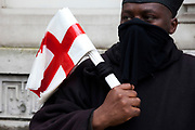 Black protester demonstrates against ethnic codes used by the police. Claiming that 'Everything is white on Whitehall'. Whan asked what racial code he is he says 'IC4 - Black'. London, UK.