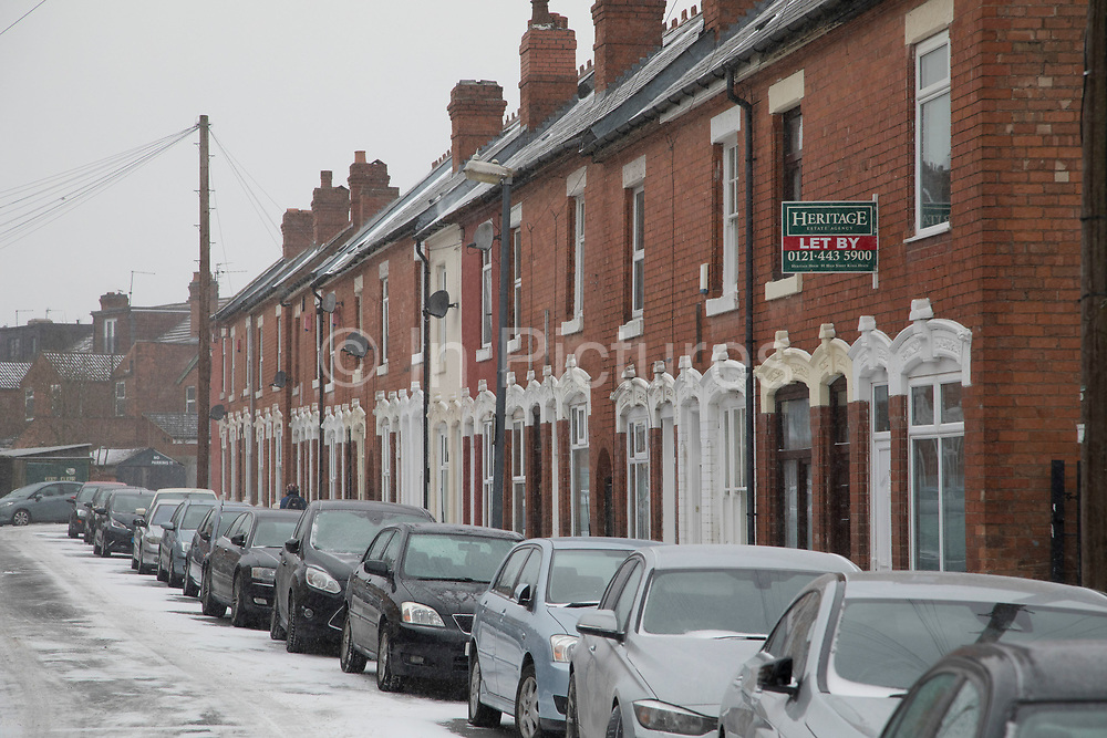 Terraced housing and parked cars during freezing weather, dubbed 'The Beast from the East' due to the sub zero cold temperature winds coming in from Siberia, descends on Kings Heath High Street on 1st March 2018 in Birmingham, United Kingdom.