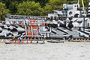 Boats pass HMS President which has been painted in 'Dazzle' camouflage paint in commemoration of WW1, The Great River Race, London's River Marathon (also known as The UK Traditional Boat Championship) - a 21.6 Miles boat race up the River Thames from London Docklands to Ham in Surrey. It attracts over 300 crews from all over the globe and appeals to every level of competitor from those who enjoy fun, fancy dress and charity stunts, to serious sportsmen. River Thames, London, 27 September 2014.