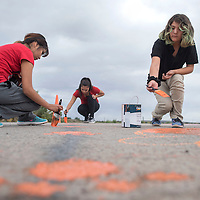 From left Chastity Craig, Jasielle Yazzie and Payson Nez work on painting the sophomore's class pride tile on the street in front of Gallup High School in Gallup Tuesday as part of the school's week long homecoming celebrations.