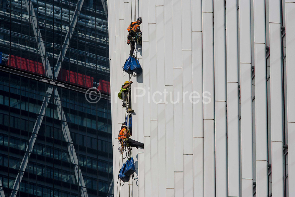 Window cleaner abseilers lower themselves down the Walkie Talkie building in the City of London. Making their way steadily down the western face of one of London's newest city buildings, the team of window cleaners attending to the plate glass surfaces which already require attention high above London's streets. With equipment hanging below their feet, they edge slowly and safely to the ground using a system of ropes, harnesses and carabiners. 20 Fenchurch Street is a 37-storey building 160 m (525 ft) tall, commercial skyscraper taking its nickname because of its distinctive shape.