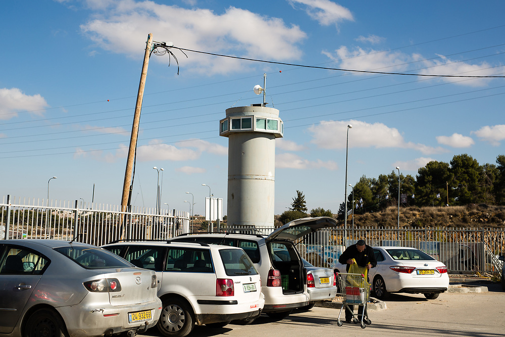 An Israeli military watchtower is seen behind a Jewish customer loading groceries from a supermarket cart into his car in the parking lot of a recently opened shopping center located at the Gush Etzion junction, near the West Bank Jewish settlement of Efrat in the Gush Etzion settlement bloc, which is situated on the southern outskirts of the Palestinian West Bank city of Bethlehem, on December 30, 2016.