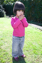 Little girl standing in the garden,