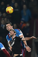 Niall Canavan of Scunthorpe United gets to the ball before Will Grigg of Wigan Athletic  during the Sky Bet League 1 match between Scunthorpe United and Wigan Athletic at Glanford Park, Scunthorpe, England on 2 January 2016. Photo by Ian Lyall.