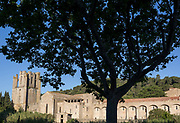 The Abbey of Sante-Marie DOrbieu in the pretty French medieval walled village of Lagrasse on the River Orbieu, on 24th May, 2017, in Lagrasse, Languedoc-Rousillon, south of France. Lagrasse is listed as one of Frances most beautiful villages and lies on the famous Route 20 wine route in the Basses-Corbieres region dating to the 13th century.