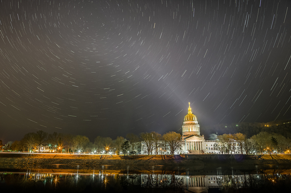 The capitol building of Charleston, West Virginia sits along the Ohio River with the night sky bedazzled in stars, their motion shown in this long exposure shot, as a spot light illuminates the building's gold capped crown, extending it's light to Polaris, the ever-present north star.