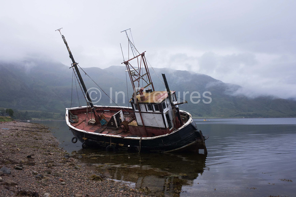 An abandoned coastal fishing boat lies askew in waters of Inverscaddle Bay, Ardgour, Scotland. On a bleak and grey summer evening, with low clouds descending on surrounding hills and mountains, we see the still waters of this Scottish lake lapping against the hull of this vessel that appears to have ended its days washed up on the beach. It is low-tide because this waterway connects to the wider sea of the Western Isles. Fisheries have always been an important sector of Scottish communities' lives so when there is an economic recession for example, the livelihoods of those employed on-board trawlers and boats like these are first hit.