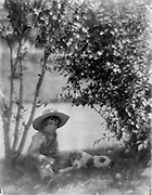 Photograph of a Boy with a dog, a study made at Oceanside. Black and White. The boy is wearing overalls and a hat, sat next to a tree on the ground. The dog sits next to him in the shadow of shrubbery. In the background is a pond. Circa 1904 Gertrude Käsebier, 1852-1934, photographer.
