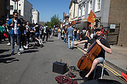 Busker playing cello on Portobello Road Market in Notting Hill, West London, England, United Kingdom. People enjoying a sunny day out hanging out at the famous Sunday market, when the antique stalls line the street.  Portobello Market is the worlds largest antiques market with over 1,000 dealers selling every kind of antique and collectible. Visitors flock from all over the world to walk along one of Londons best loved streets.