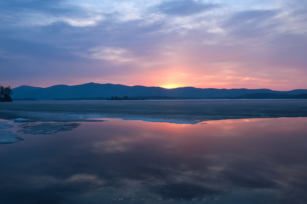 Lake George, Adirondacks, NY.   The ice is receding around the edges of the lake, pulling inward to the center where the water is the coldest, giving up it's acrage grudgingly to vernal urgings. Just before the sun breaches the dip in the range that borders the east side of the lake, I sit alone in the stillness, waiting for the wind to stir as it always does at sunrise.  A small puff and some whispers will break the silence, as when the lights come on in a darkened theater and the crowd feels like they have to comment.  I expect it, it rolls over my shoulders, past my ears, like so much noise.  Every morning is revealed differently, each revelation produces an opinion.  I am locked on what I see.  The wind will murmur out to the iceline, soon to be gone.