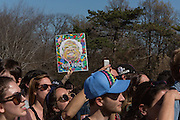 "Brooklyn, NY - 17 April 2016. A hand holds high a poster showing Bernie Sanders' face with the text ""Our Voice."" Vermont Senator Bernie Sanders, who is running as a Democrat in the U.S. Presidential primary elections, held a campaign ""get out the  vote"" rally in Brooklyn's Prospect Park."