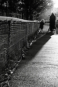 A woman and her young daughter walk along a footpath in the sun on a sunny autumn afternoon in Parsons Green, South-West London