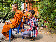 15 MARCH 2015 - SIEM REAP, SIEM REAP, CAMBODIA: A Buddhist monk and his assistant at the annual mass merit making at Wat Bo in Siem Reap. More than 1,200 Buddhist monks, from across Siem Reap province, received alms from Buddhist lay people during the morning long ceremony. Wat Bo was originally built to be a the temple for Siamese (Thai) troops when Siem Reap and western Cambodia were controlled by Siam (Thailand). Now Wat Bo is one of the most important temples in Siem Reap.      PHOTO BY JACK KURTZ