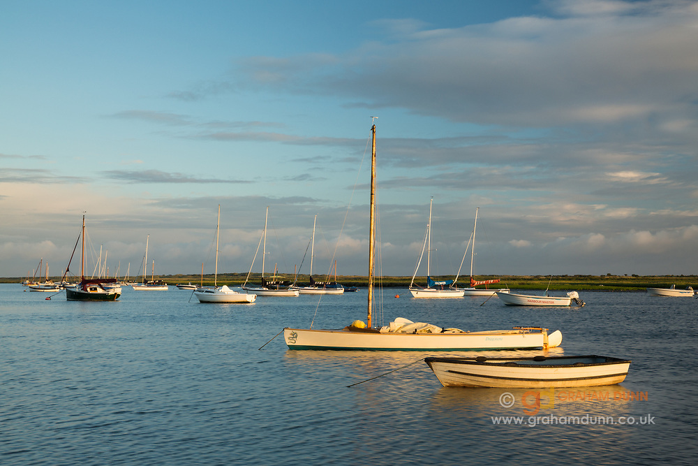 Moored sailing boats in Brancaster Staithe harbour catch the golden light at sunrise. A high tide scene in North Norfolk, East Anglia, England, UK.