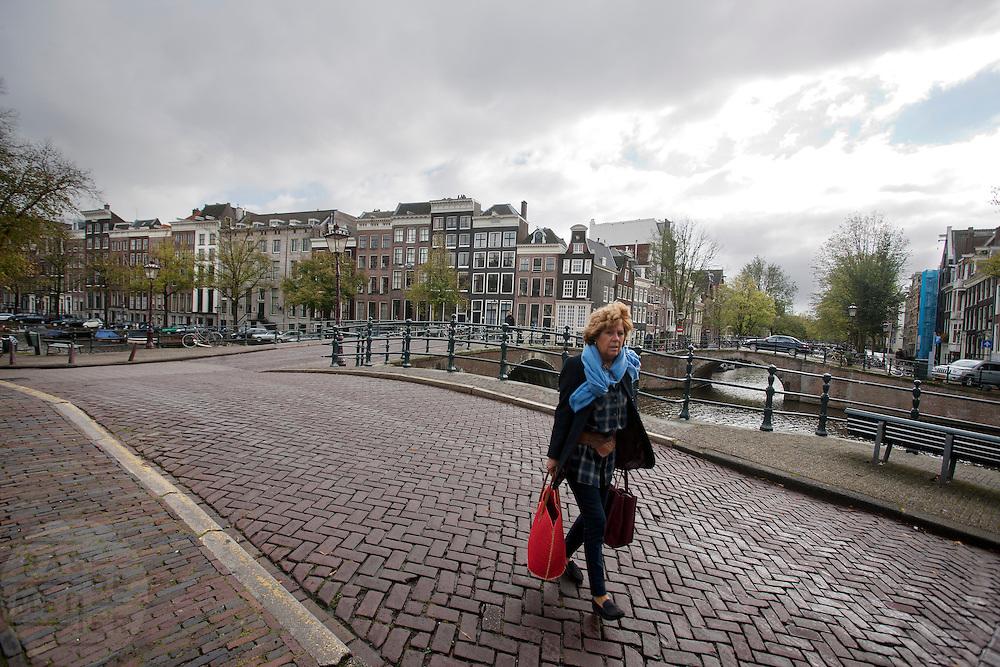 Een vrouw loopt over de Keizersgracht in Amsterdam.<br /> <br /> A woman is walking at the Keizersgracht in Amsterdam.