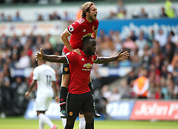 Manchester United's Romelu Lukaku (bottom) celebrates scoring his side's second goal with team-mate Daley Blind during the Premier League match at the Liberty Stadium, Swansea.
