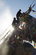 Two Tibetan men hang prayer flags near the Namgyal Tsemo Gompa in Leh, India.