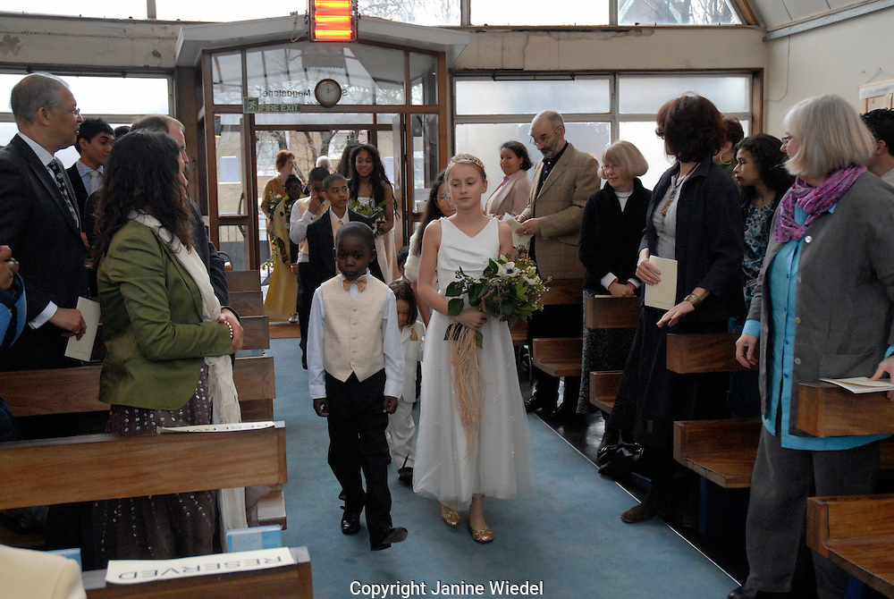 Flower girl and boy coming down aisle during wedding service in church.
