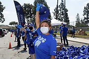 Netflix actress Annie Gonzalez greets motorists at the Dodger Day Drive-Thru at Belvedere Park, Tuesday, June 30, 2020, in Los Angeles. The event was hosted by The Los Angeles Dodgers Foundation, which distributed food boxes, books, sports equipment, clothing, toys and hygiene supplies to more than 1,000 registered youth from the Boyle Heights, East Los Angeles, La Puente and Monterey Park communities.
