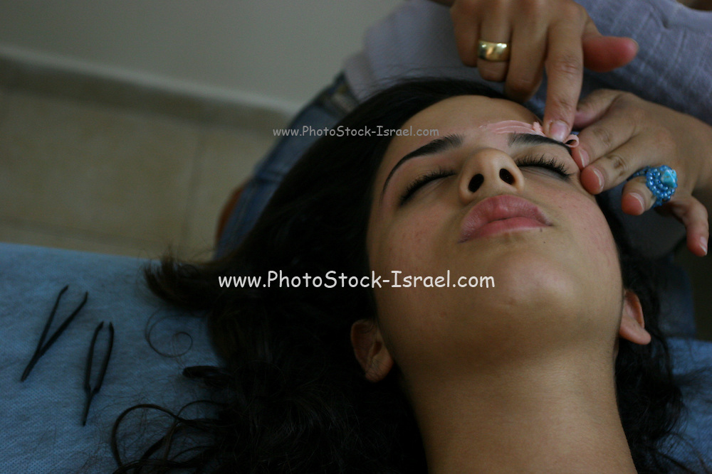 Woman has her eyebrows shaped at a beautician