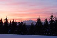 Colorful cloud striations adorn the sky above the Iliamna Volcano, Alaska