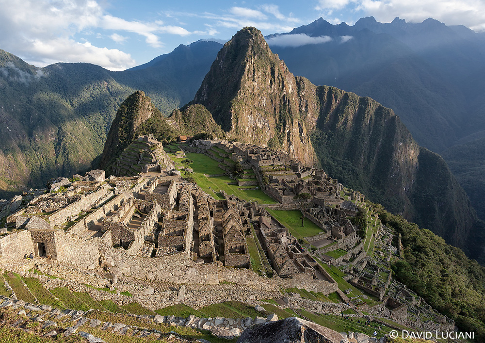 View over Machu Picchu just after sunrise with Huayna Picchu Mountain at the background and the main gate entrance, visible at the left side of the photo.