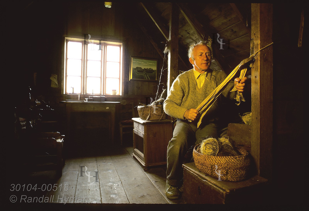 Thord Tomasson, director @ Skogar museum, pulls hide thru ram's horn;old way of softening vellum Iceland