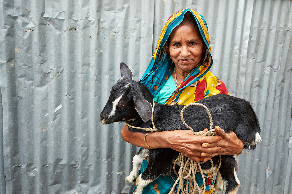 Jamela Khatun holds her goat in West Fasura, a village on an island in the Brahmaputra River in northern Bangladesh. Severe flooding in August 2017 destroyed the island's crops but RDRS Bangladesh, a member of the ACT Alliance, provided emergency cash grants to Khatun and other vulnerable island residents so they could reestablish their household economies and restart their lives. Khatun, who lost her house and animals to the flood waters, used her cash grant to buy food, the goat, and pay some of her children's education costs.