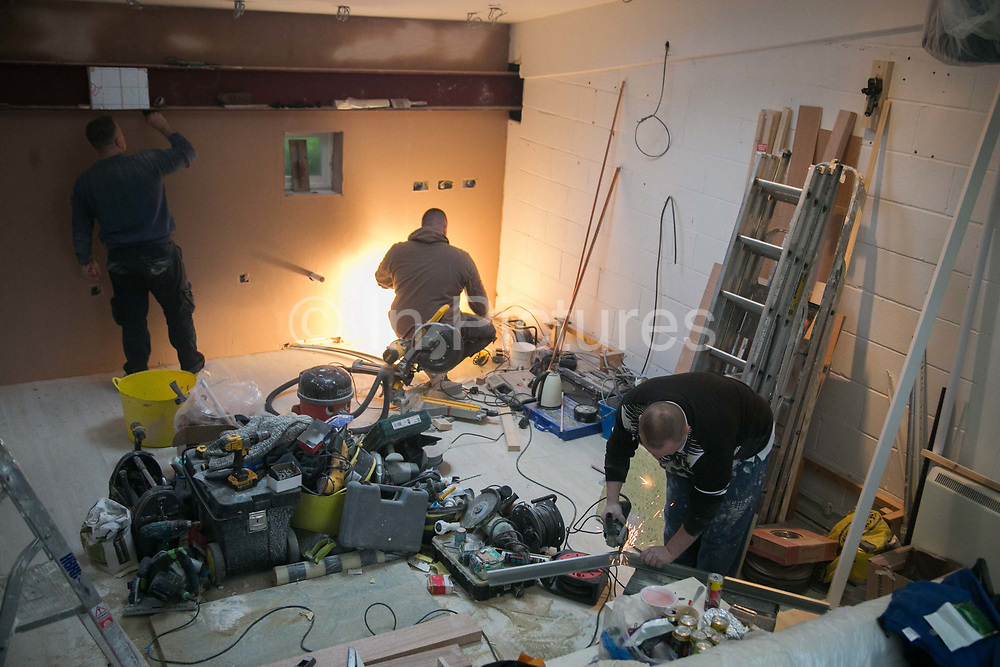 Polish builders at work in a flat in Hackney on 17th February in London, United Kingdom. Dawid Krasuwski R and his Polish colleagues are all highly skilled builders and have lived and worked in London for years.