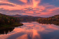 Beautiful sunset clouds and peak fall color on Wrightsville Reservoir in northern Vermont, USA