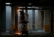 Construction worker welds steel I-beam girders at a construction site