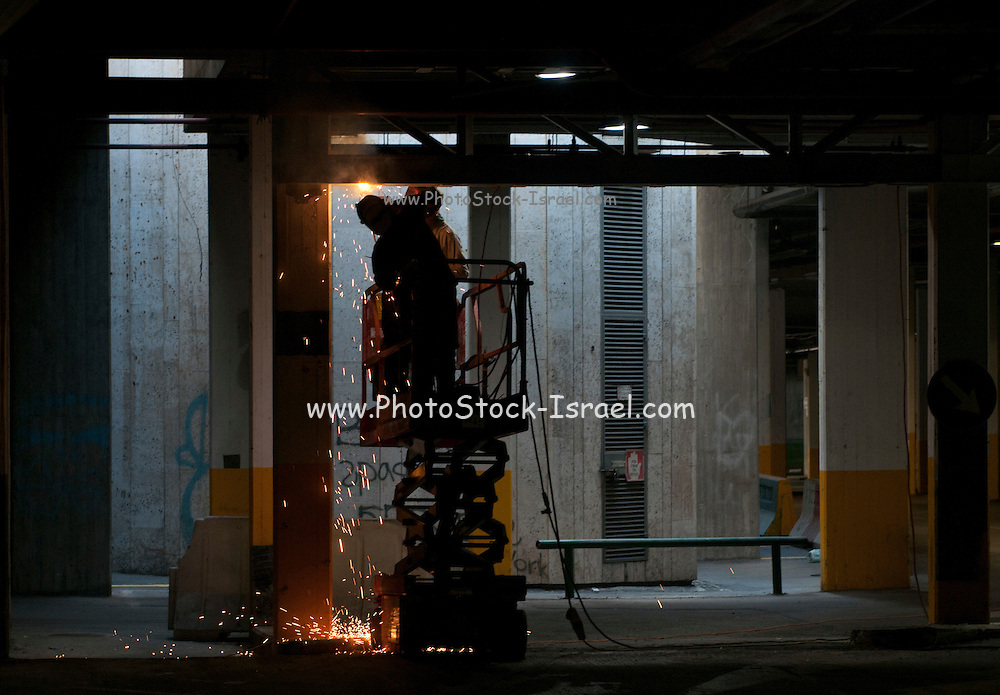 Construction worker welds steel I-beam girders at a construction site