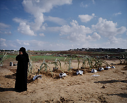 A woman is seen visiting the grave of several relatives who were killed by Israeli artillery fire, Beit Hanoun, Gaza Strip, Palestinian Territories, Nov. 24, 2006. Israel blames the deaths on a targeting error and expresses regret. According to Human Rights Watch, since September 2005, Israel has fired about 15,000 rounds at Gaza while Palestinian militants have fired around 1,700 back.