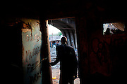 "In this Aug. 12, 2012 photo, a crack user leaves a crack house near the Manguinhos slum in Rio de Janeiro, Brazil. <br /> <br /> <br />  The South American country began experiencing a public health emergency in recent years as demand for crack boomed and open-air ""cracolandias,"" or crack lands, popped up in the sprawling urban centers of Rio and Sao Paulo, with hundreds of users gathering to smoke the drug. The federal government announced in early 2012 that more than $2 billion would be spent to fight the epidemic, with the money spent to train local health care workers, purchase thousands of hospital and shelter beds for emergency treatment, and create transitional centers for recovering users."