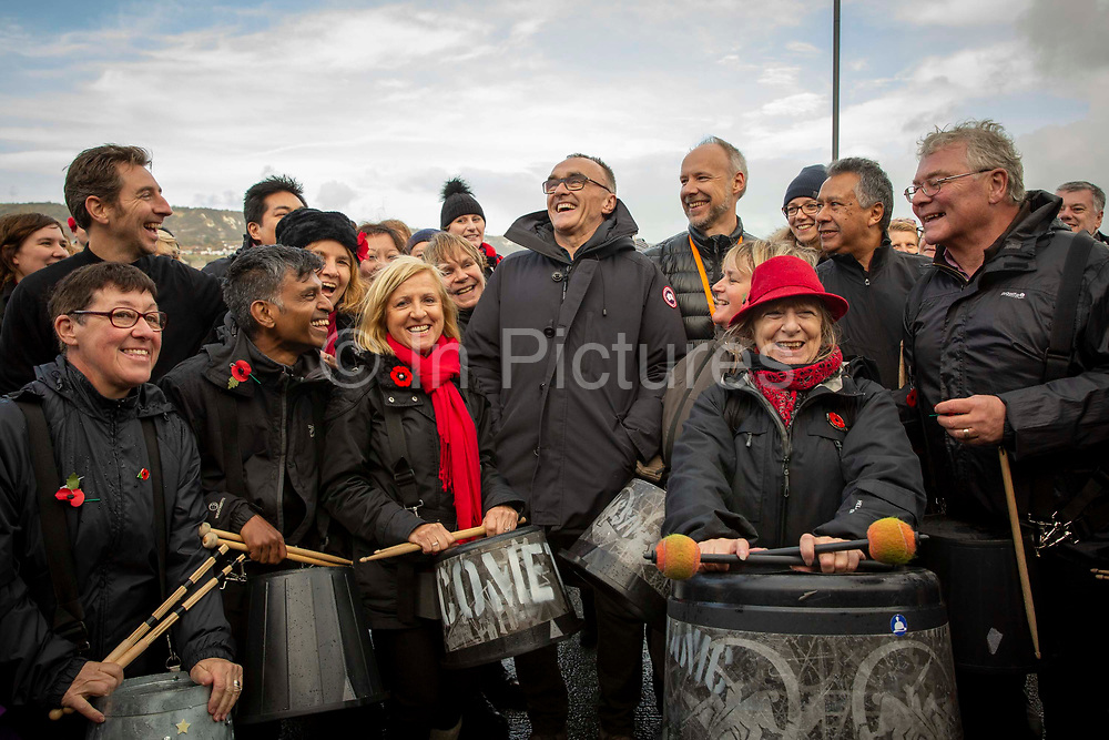 Danny Boyle with the Pandemonium Drummersfrom the London 2012 Olympic Ceremonies perform Symphony of Waves created forthe Armistice Day centenary remembrance event 'Pages of the Sea'onFolkestone Harbour Arm, Folkestone Kent. 11th November 2018. Presented by over 40 drummers, the semi-improvised piece explores the concern, anxiety, and commitment of those who left home and started a journey across the sea to fight in World War One, from which many did not return. Performed on buckets and bins is is designed to evoke memories of a pleasant land left behind and outlooks of an uncertain future.