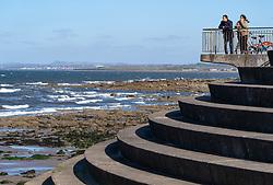 Portobello beach and promenade near Edinburgh during Coronavirus lockdown on 19 April 2020. Couple look out from pavilion viewpoint on beach.