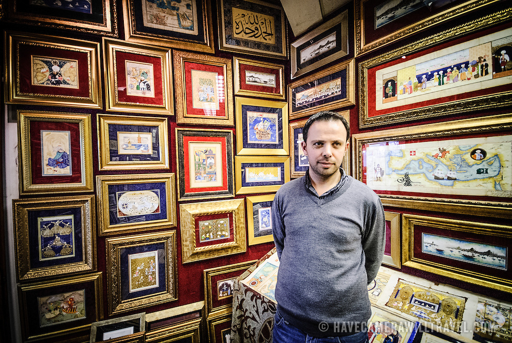 Shopkeeper poses with the illuminations and illustrations on display on the walls of the Sahaflar Çars (Antique Book Bazaar) next o the Grand Bazaar in Istanbul, Turkey.
